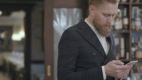 Πορτρέτο ενός επιτυχούς νέου γενειοφόρου βέβαιου επιχειρηματία που δακτυλογραφεί σε ένα τηλέφωνο κυττάρων στεμένος σε ένα εστιατό απόθεμα βίντεο