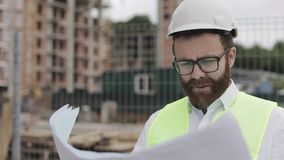 Πορτρέτο ενός επιτυχούς νέου μηχανικού ή ενός αρχιτέκτονα που φορά ένα άσπρο κράνος, που κοιτάζει στα κατασκευαστικά σχέδια σε δι φιλμ μικρού μήκους