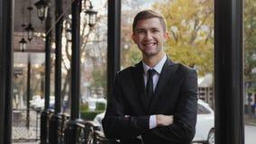 Πορτρέτο ενός επιτυχούς χαμογελώντας νέου επιχειρηματία υπαίθρια φιλμ μικρού μήκους