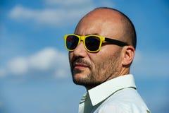 Πορτρέτο ενός επιχειρηματία στα σύγχρονα γυαλιά ηλίου ενάντια σε ένα μπλε SK Στοκ φωτογραφία με δικαίωμα ελεύθερης χρήσης