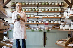 Πορτρέτο ενός ευτυχούς ανώτερου εμπόρου που στέκεται με το βάζο καρυκευμάτων στο κατάστημα Στοκ Εικόνες