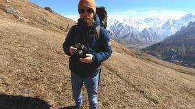 Πορτρέτο ενός ευτυχούς γενειοφόρου ταξιδιωτικού φωτογράφου στα γυαλιά ηλίου και ενός καπέλου με μια ανακλαστική κάμερα στα χέρια  απόθεμα βίντεο