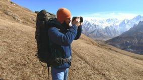 Πορτρέτο ενός ευτυχούς γενειοφόρου ταξιδιωτικού φωτογράφου στα γυαλιά ηλίου και ενός καπέλου με μια ανακλαστική κάμερα στα χέρια  φιλμ μικρού μήκους