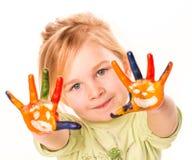 Πορτρέτο ενός ευτυχούς εύθυμου κοριτσιού που εμφανίζει χέρια της που χρωματίζονται στα φωτεινά χρώματα Στοκ φωτογραφία με δικαίωμα ελεύθερης χρήσης