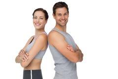 Πορτρέτο ενός ευτυχούς κατάλληλου νέου ζεύγους με τα χέρια που διασχίζονται στοκ φωτογραφία