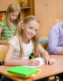 Πορτρέτο ενός ευτυχούς κοριτσιού που γράφει σε ένα βιβλίο άσκησης κατά τη διάρκεια του διαγωνισμού Στοκ εικόνα με δικαίωμα ελεύθερης χρήσης