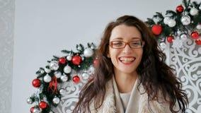 Πορτρέτο ενός ευτυχούς κοριτσιού brunette που φορά eyeglasses και το θερμό πουλόβερ στο υπόβαθρο του ντεκόρ Χριστουγέννων σγουρό  φιλμ μικρού μήκους