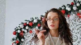 Πορτρέτο ενός ευτυχούς κοριτσιού brunette που φορά eyeglasses και το θερμό πουλόβερ στο υπόβαθρο του ντεκόρ Χριστουγέννων σγουρό  απόθεμα βίντεο