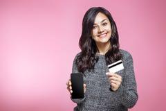 Πορτρέτο ενός ευτυχούς κοριτσιών εκμετάλλευσης κενού τηλεφώνου και της παρουσίασης οθόνης κινητού πιστωτικής κάρτας πέρα από το ρ στοκ φωτογραφίες με δικαίωμα ελεύθερης χρήσης