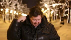 Πορτρέτο ενός ευτυχούς νεαρού άνδρα που κτενίζει την τρίχα υπαίθρια κατά τη διάρκεια του κρύου χειμερινού βραδιού απόθεμα βίντεο