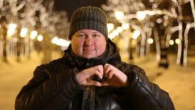 Πορτρέτο ενός ευτυχούς νεαρού άνδρα που παρουσιάζει χειρονομία αγάπης υπαίθρια κατά τη διάρκεια του κρύου χειμερινού βραδιού απόθεμα βίντεο