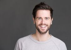 Πορτρέτο ενός ευτυχούς νεαρού άνδρα που χαμογελά στο γκρίζο υπόβαθρο Στοκ εικόνες με δικαίωμα ελεύθερης χρήσης