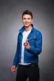 Πορτρέτο ενός ευτυχούς νεαρού άνδρα που χαμογελά στο γκρίζο υπόβαθρο Στοκ φωτογραφία με δικαίωμα ελεύθερης χρήσης