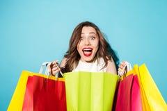 Πορτρέτο ενός ευτυχούς συγκινημένου κοριτσιού που κρατά τις ζωηρόχρωμες τσάντες αγορών Στοκ Εικόνα