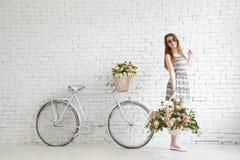 Πορτρέτο ενός ευτυχούς όμορφου νέου κοριτσιού με το εκλεκτής ποιότητας ποδήλατο και τα λουλούδια Στοκ εικόνα με δικαίωμα ελεύθερης χρήσης