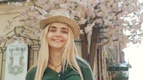 Πορτρέτο ενός ευτυχούς όμορφου ξανθού κοριτσιού με τα γυαλιά, ένα καπέλο και ένα σακάκι τζιν παντελόνι φιλμ μικρού μήκους