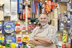 Πορτρέτο ενός ευτυχούς ώριμου πωλητή με τα όπλα που διασχίζονται στο κατάστημα υλικού Στοκ εικόνες με δικαίωμα ελεύθερης χρήσης