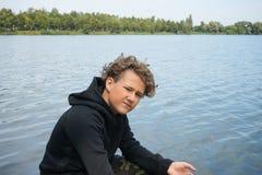 Πορτρέτο ενός εφήβου που αλιεύει στις όχθεις του ποταμού ή της λίμνης Χαριτωμένο αγόρι με τη σγουρή τρίχα στοκ εικόνες
