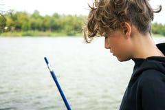 Πορτρέτο ενός εφήβου που αλιεύει στις όχθεις του ποταμού ή της λίμνης Χαριτωμένο αγόρι με τη σγουρή τρίχα στοκ φωτογραφία