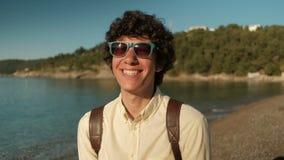 Πορτρέτο ενός εύθυμου σγουρού ατόμου στα μοντέρνα γυαλιά ηλίου στην παραλία απόθεμα βίντεο