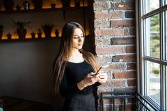 Πορτρέτο ενός εύθυμου smartphone και της εξέτασης εκμετάλλευσης γυναικών το παράθυρο στο κατάστημα καφέδων Στοκ φωτογραφία με δικαίωμα ελεύθερης χρήσης