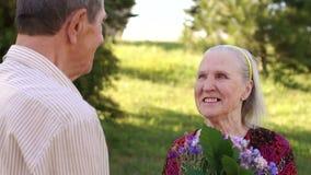 Πορτρέτο ενός ηλικιωμένου ζεύγους που περπατά στο πάρκο φιλμ μικρού μήκους