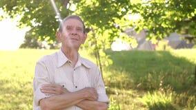 Πορτρέτο ενός ηλικιωμένου ατόμου σε ένα ηλιόλουστο πάρκο απόθεμα βίντεο