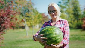 Πορτρέτο ενός θηλυκού αγρότη που κρατά ένα μεγάλο καρπούζι, εξετάζοντας τη κάμερα, χαμόγελο απόθεμα βίντεο