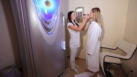 Πορτρέτο ενός θηλυκού cosmetologist με έναν πελάτη σε ένα τεχνητό δωμάτιο μαυρίσματος απόθεμα βίντεο