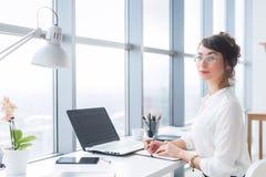 Πορτρέτο ενός θηλυκού συγγραφέα που εργάζεται στο γραφείο, που χρησιμοποιεί το lap-top, που φορά τα γυαλιά Νέος υπάλληλος που προ στοκ φωτογραφία με δικαίωμα ελεύθερης χρήσης