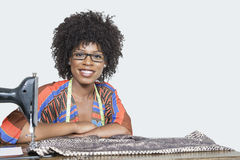Πορτρέτο ενός θηλυκού σχεδιαστή μόδας αφροαμερικάνων με τη ράβοντας μηχανή και του υφάσματος πέρα από το γκρίζο υπόβαθρο Στοκ Εικόνες