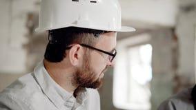 Πορτρέτο ενός ικανοποιημένου επιχειρηματία σε ένα κράνος στο κεφάλι του, το οποίο συζητά την ολοκλήρωση του εργοτάξιου οικοδομής  απόθεμα βίντεο