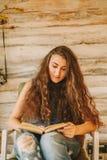 Πορτρέτο ενός κοριτσιού με τη μακριά, σγουρή, φυσική τρίχα Ανάγνωση κοριτσιών Στοκ Φωτογραφία