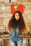 Πορτρέτο ενός κοριτσιού με τη μακριά, σγουρή, φυσική τρίχα Κόκκινος κόκκορας στοκ φωτογραφία