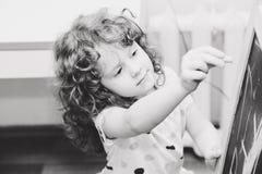 Πορτρέτο ενός κοριτσιού που γράφει σε έναν πίνακα κιμωλίας. Στοκ Εικόνα