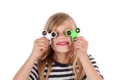 Πορτρέτο ενός κοριτσιού που παίζει με δύο fidget κλώστες Στοκ Φωτογραφίες