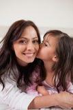 Πορτρέτο ενός κοριτσιού που φιλά τη μητέρα της Στοκ Εικόνα