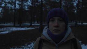 Πορτρέτο ενός κοριτσιού σε ένα κρύο σκοτεινό χειμερινό δάσος απόθεμα βίντεο