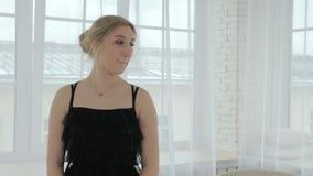 Πορτρέτο ενός κοριτσιού σε ένα μαύρο φόρεμα σε ένα φωτεινό δωμάτιο απόθεμα βίντεο