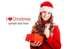 Πορτρέτο ενός κοριτσιού στα ενδύματα Χριστουγέννων με ένα δώρο διαθέσιμο στο απομονωμένο άσπρο υπόβαθρο Στοκ φωτογραφία με δικαίωμα ελεύθερης χρήσης