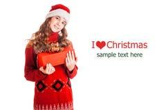Πορτρέτο ενός κοριτσιού στα ενδύματα Χριστουγέννων με ένα δώρο διαθέσιμο στο απομονωμένο άσπρο υπόβαθρο Στοκ Εικόνες