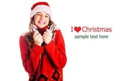 Πορτρέτο ενός κοριτσιού στα ενδύματα Χριστουγέννων με ένα δώρο διαθέσιμο στο απομονωμένο άσπρο υπόβαθρο Στοκ Φωτογραφία