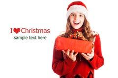 Πορτρέτο ενός κοριτσιού στα ενδύματα Χριστουγέννων με ένα δώρο διαθέσιμο στο απομονωμένο άσπρο υπόβαθρο Στοκ εικόνα με δικαίωμα ελεύθερης χρήσης