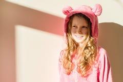 Πορτρέτο ενός κοριτσιού στις μαλακές θερμές ρόδινες πυτζάμες Κορίτσι 7 χρονών, ξανθό με τη μακριά σγουρή τρίχα, σε μια κουκούλα,  στοκ εικόνες