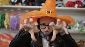 Πορτρέτο ενός κοριτσιού στο καπέλο της μάγισσας σε μια λεωφόρο αγορών Χριστουγέννων απόθεμα βίντεο