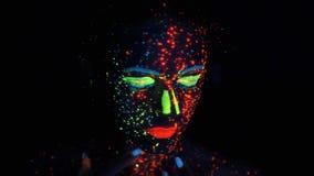 Πορτρέτο ενός κοριτσιού στο φως νέου το πρόσωπο ενός όμορφου κοριτσιού είναι χρωματισμένο με τα χρώματα πυράκτωσης απόθεμα βίντεο
