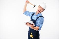 Πορτρέτο ενός κραυγάζοντας οικοδόμου που προσπαθεί να σπάσει την ταμπλέτα PC Στοκ φωτογραφία με δικαίωμα ελεύθερης χρήσης