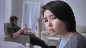 Πορτρέτο ενός λυπημένου καταθλιπτικού ασιατικού κοριτσιού, πιωμένος σύζυγος στο υπόβαθρο που προσέχει τη TV, που εξετάζει τη κάμε φιλμ μικρού μήκους