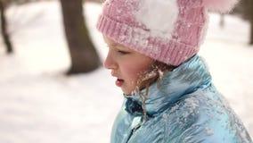 Πορτρέτο ενός λυπημένου κοριτσιού με τα ίχνη χιονιάς μετά από μια πάλη χιονιού στο πάρκο Χειμερινός ελεύθερος χρόνος των παιδιών, απόθεμα βίντεο