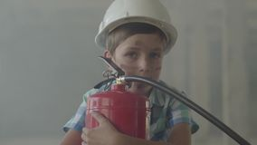 Πορτρέτο ενός μικρού αγοριού σε ένα άσπρο προστατευτικό κράνος με έναν πυροσβεστήρα που εξετάζει τη κάμερα σε ένα υπόβαθρο απόθεμα βίντεο